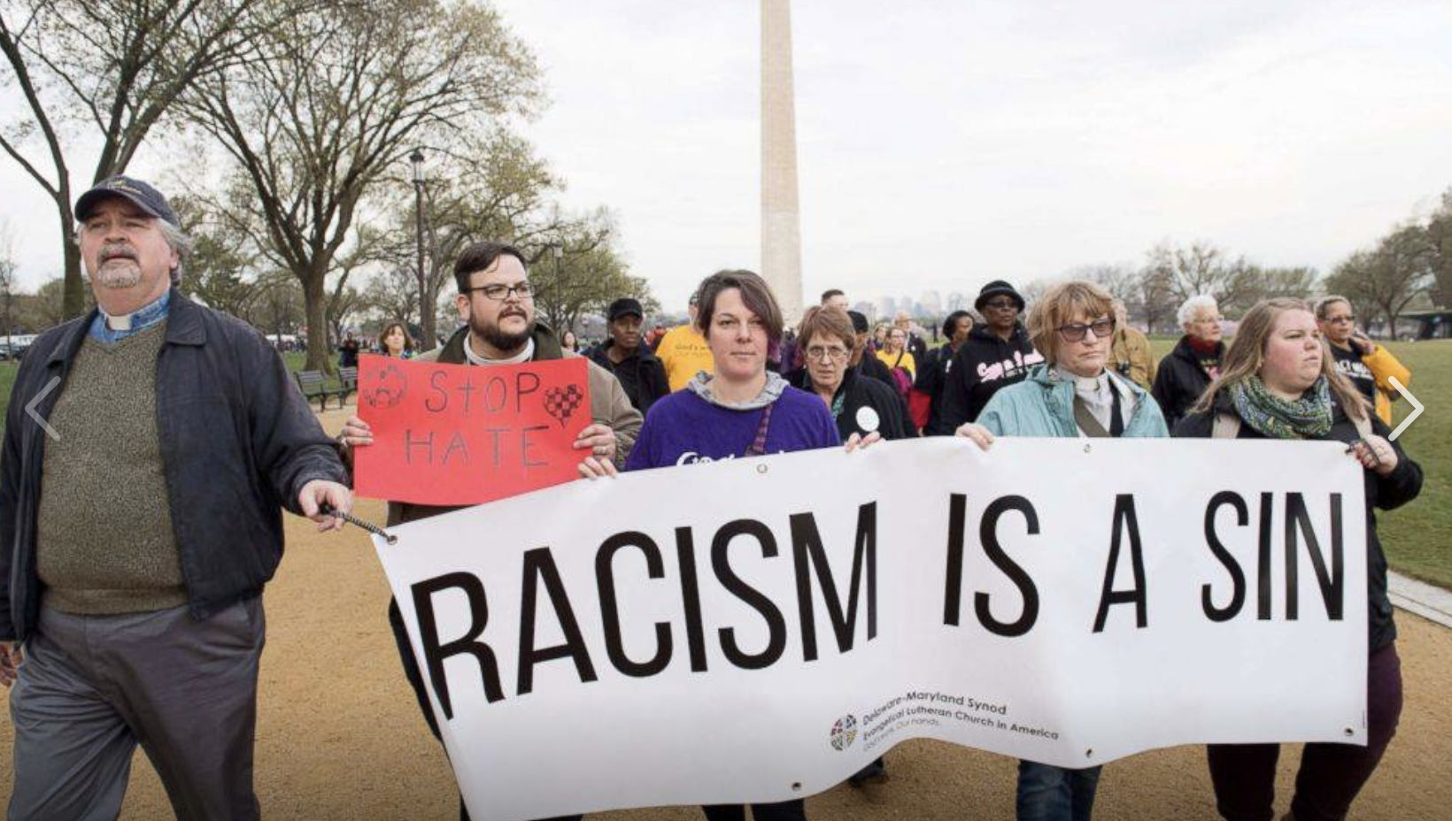 Synod leaders marching in Washington D.C. with a banner that reads 'Racism is a sin.'