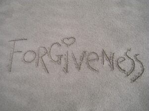 The word 'forgiveness' written in sand