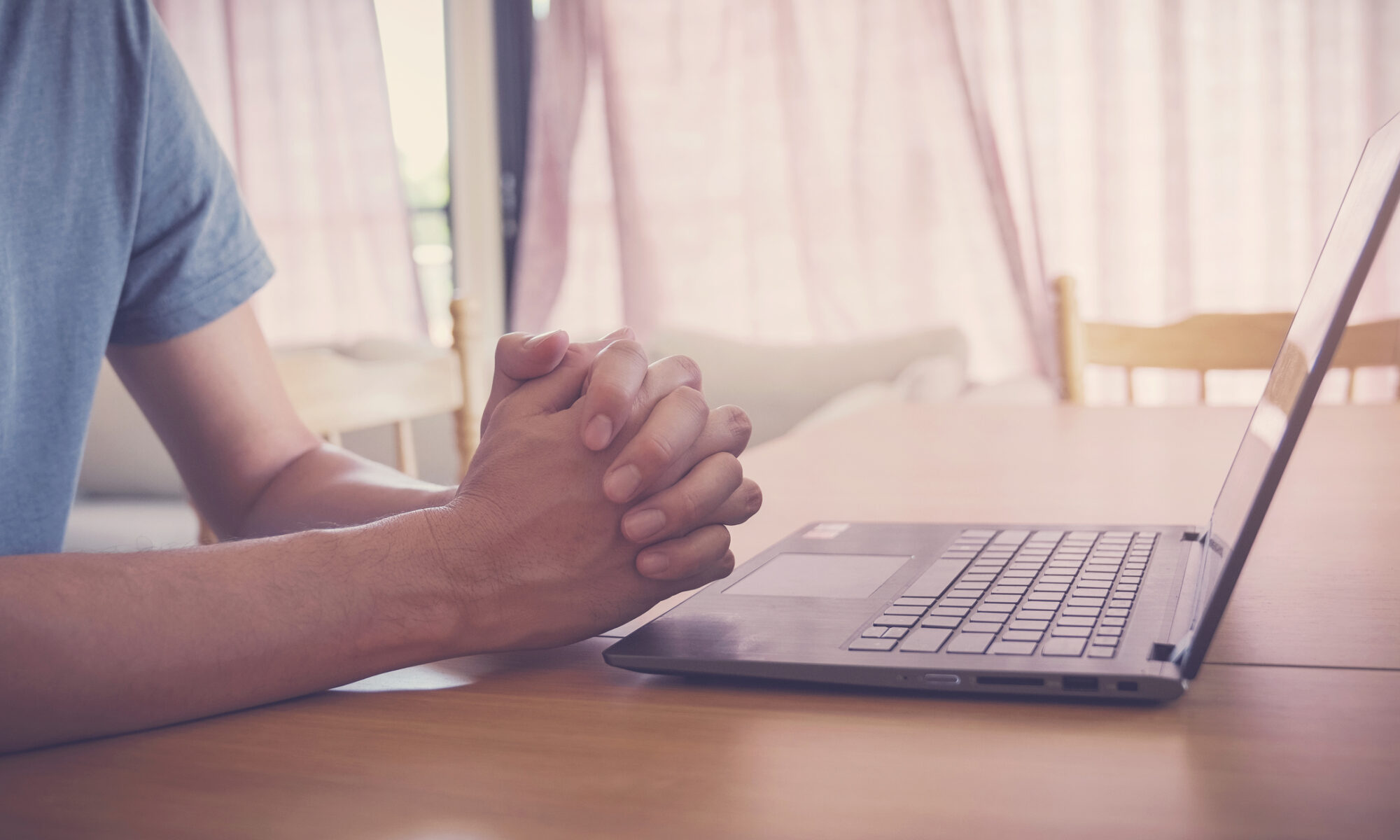 Praying hands with a laptop